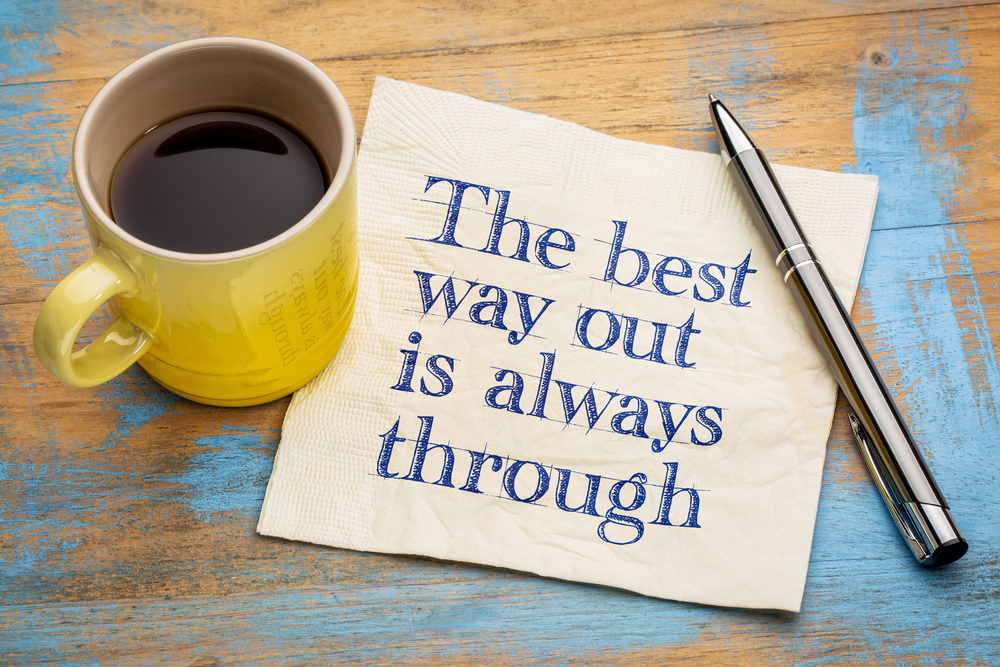 The best way out is always through - handwriting on a napkin with a cup of espresso coffee